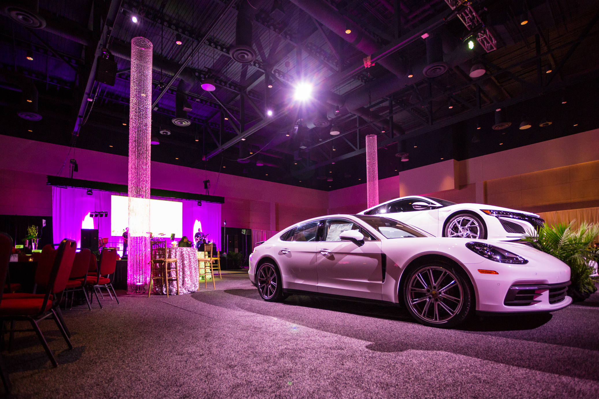 White cars on exhibit with visual equipment creating atmosphere.
